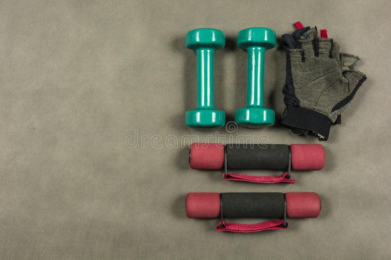 Different types of dumbbells and fingerless gloves. Different types of dumbbells for fitness or rehabilitation and fingerless gloves royalty free stock photo