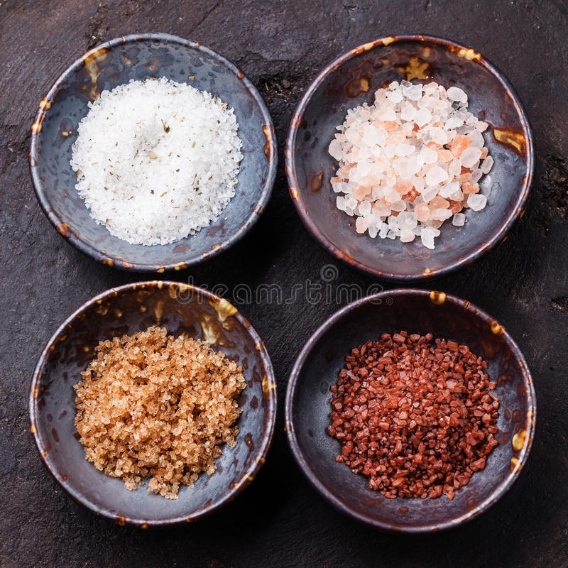 Different types of food coarse Salt. In ceramic bowls on dark background royalty free stock photo