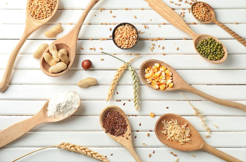 Different types of grains and cereals on white wooden table stock photos