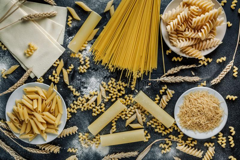 Different types of Italian pasta on a dark wooden rustic background. Mixed dry pasta and spaghetti. Still life. Rustic style. Top royalty free stock photo