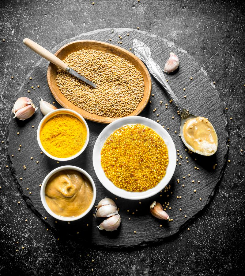 Different types of mustard on a stone Board with garlic. On dark rustic background stock images