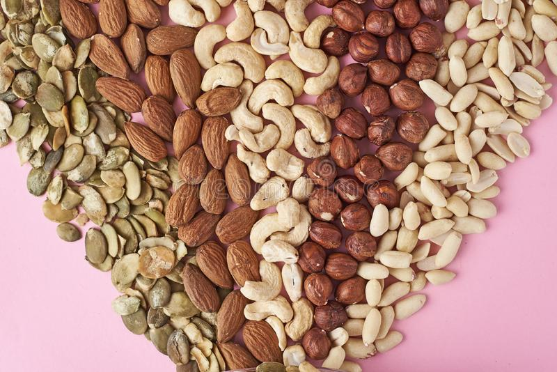 Different types of nuts and pumpkin seeds on a pink background, top view. Different types of nuts and pumpkin seeds on pink background, top view royalty free stock photos
