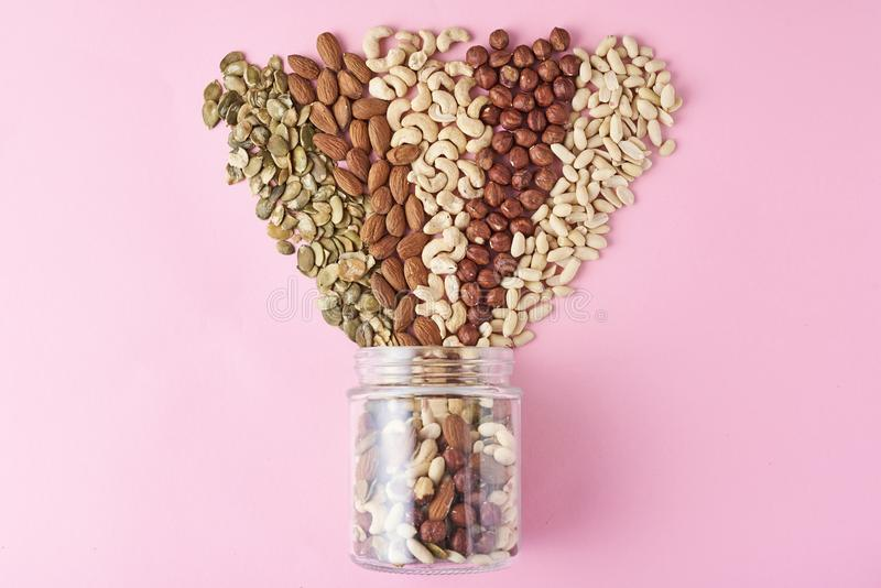 Different types of nuts and seeds in a glass jar on pink background, top view royalty free stock photo