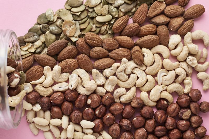 Different types of nuts and seeds in a glass jar on pink background, top view. Different types of nuts and seeds in glass jar on pink background, top view royalty free stock image