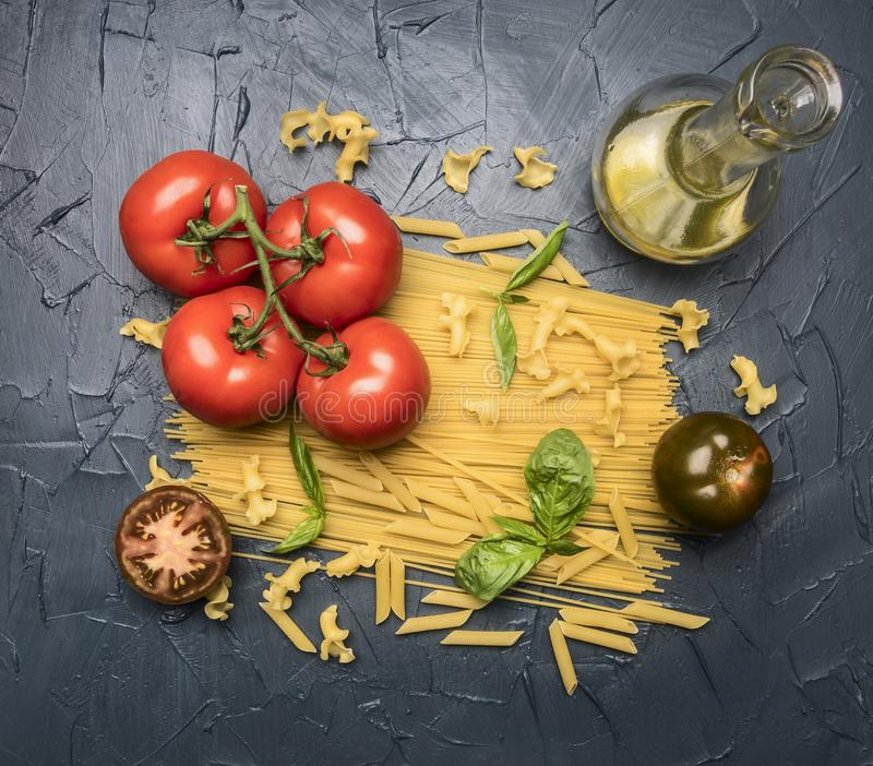 Different types of pasta, laid out with various ingredients, tomatoes, herbs, oil in a decanter and seasonings on a dark rustic ba stock image