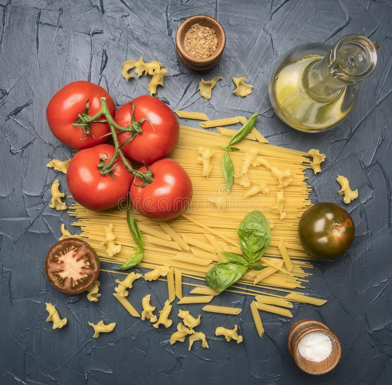 Different types of pasta, laid out with various ingredients, tomatoes, herbs, oil in a decanter seasonings on a dark rustic ba stock photos