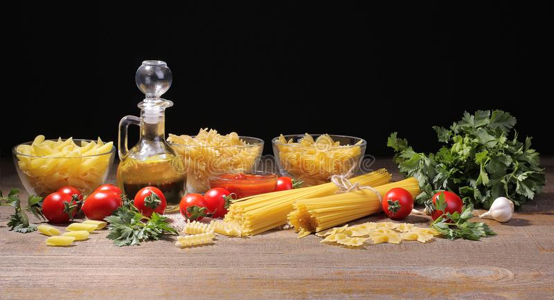Different types of pasta with cherry tomatoes, olive oil, parsley on a brown wooden background. royalty free stock photography