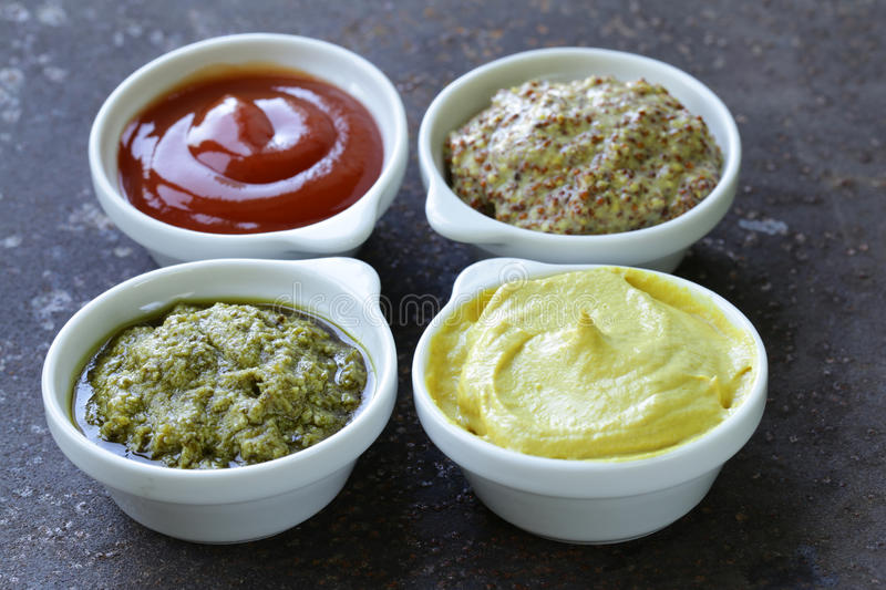 Different types of sauces. Ketchup, mustard, pesto stock images