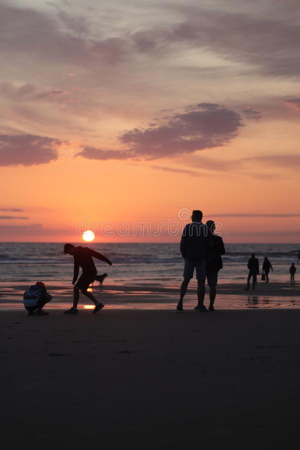 Different types of silouette people at the beach during a beautiful sunset in France montalivet royalty free stock photo