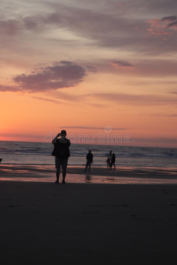 Different types of silouette people at the beach during a beautiful sunset in France montalivet. Dogs, photography, taking, reflection, down, sunrise, clouds stock photos