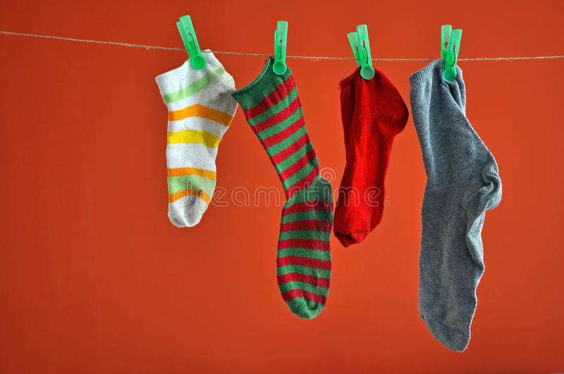 Different types of striped socks hanging isolated on red stock photos