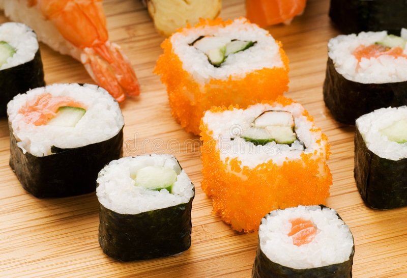 Different types of sushi. On a bamboo plate royalty free stock images