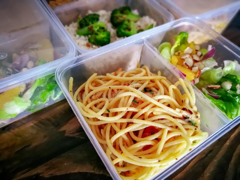 Different types of takeaway food in microwavable containers on a wooden background. These are sold in convenient stores in Malaysia stock photos