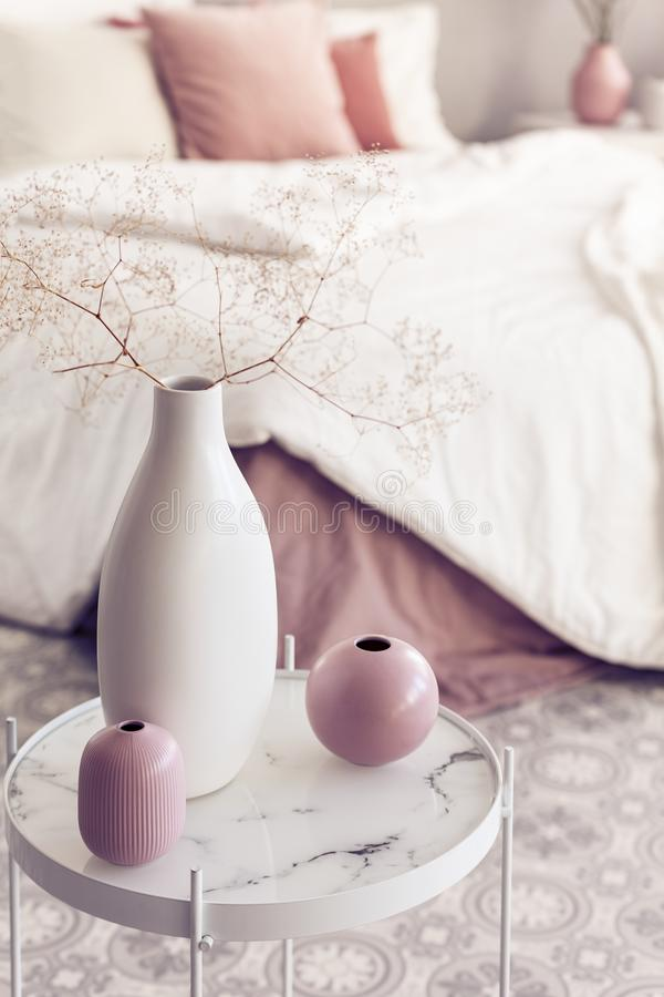 Different types of vases on small coffee table in bright bedroom interior.  royalty free stock images