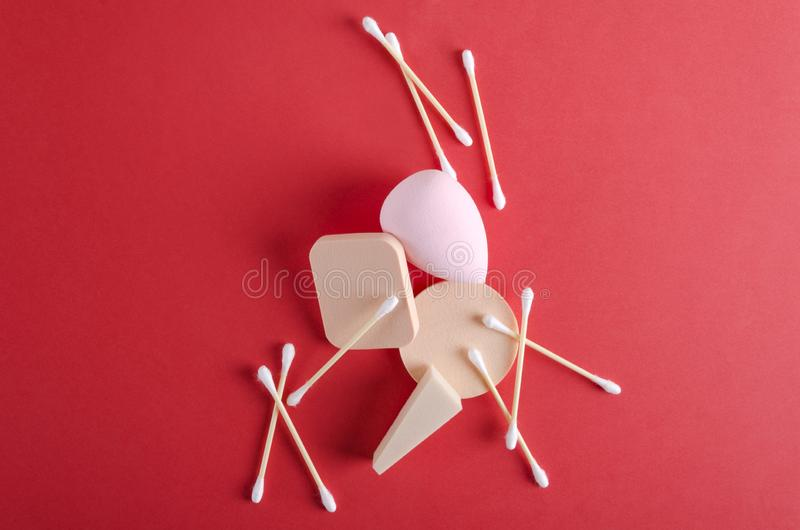 Different typies of cosmetic sponges and ear sticks on the red background.Concept of beauty treatments with various tools royalty free stock photos