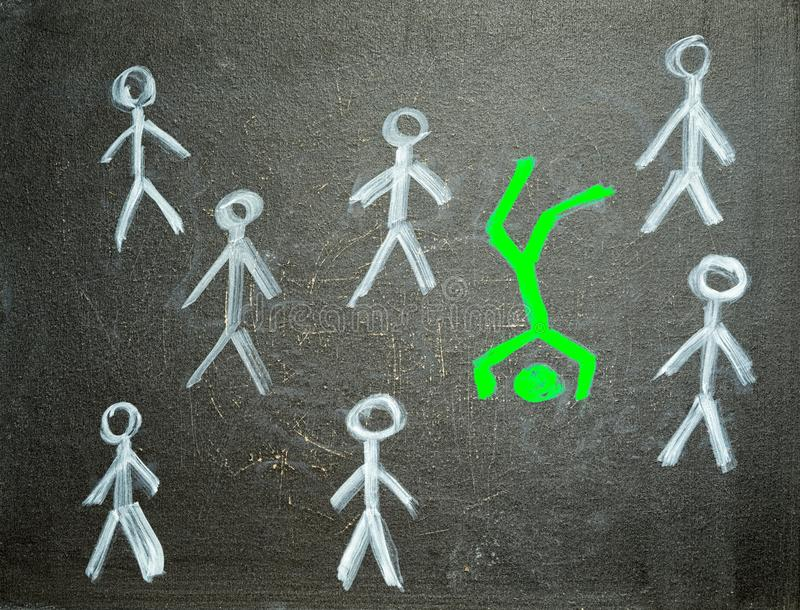 Different and unique concept. Green man standing on the head between usual white men, chalk drawing on the blackboard royalty free stock images