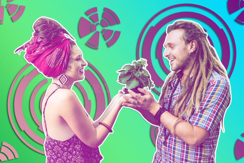 Unusual nice happy couple holding a plant together stock photo