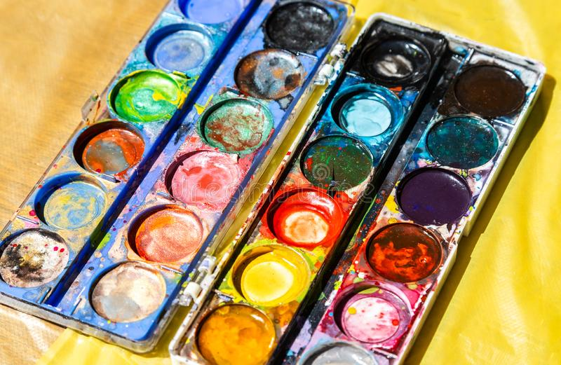 Different used colorful watercolor paint. On a yellow background royalty free stock image