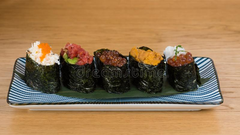 Different varieties of gunkan wrapped in nori seaweed, bluefin tuna tartare, caviar of different sizes and colours avocado, sea. Urchin and squid, served on a royalty free stock image