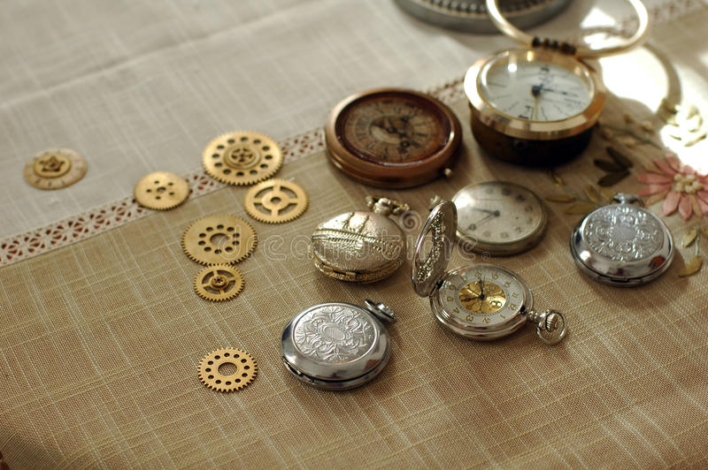 Different watches and cogwheels, gearwheels in steampunk style on a table. Cogwheels and watches, gearwheels in steampunk style on a table stock images