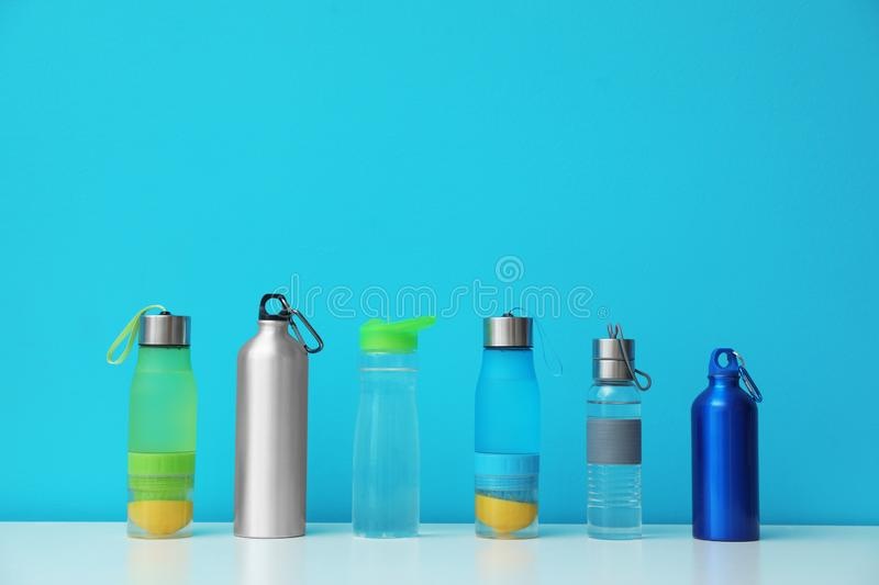Different water bottles for sports on color background. Space for text stock photography
