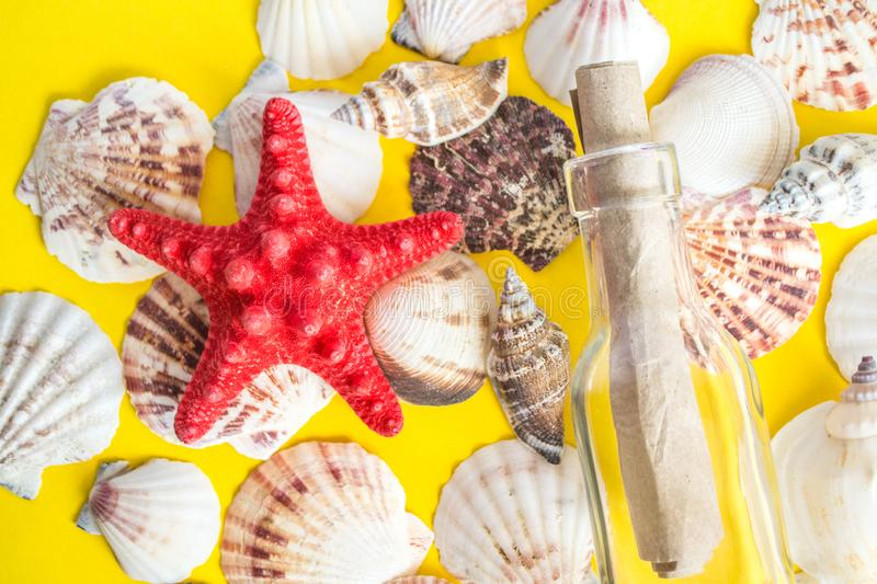 Different white seashells with message in a bottle on yellow background royalty free stock image