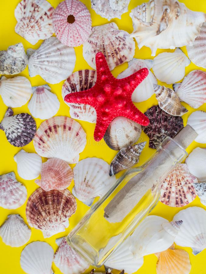 Different white seashells with message in a bottle on yellow background stock photos