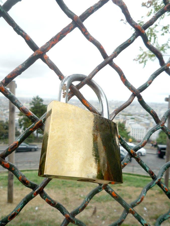 Difficulté d'or de cadenas d'amour sur un filet métallique photos libres de droits