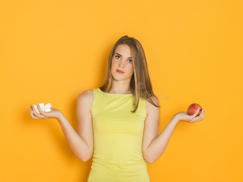 Difficult choice between sweets and healthy food stock photography
