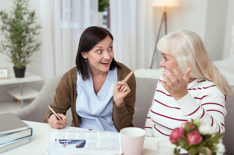 Merry elder woman and caregiver solving crossword. Difficult crossword. Appealing elder women and caregiver reading news and gossiping stock photos