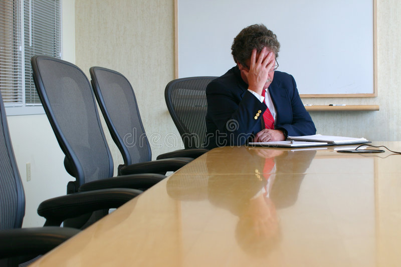 A difficult day. Businessman sitting in a conference room with his head in his hand royalty free stock images