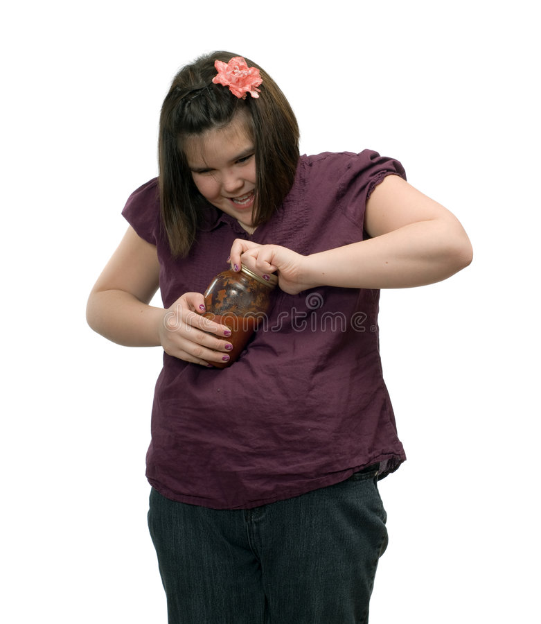 Difficult Jar To Open. A young girl having problems opening a jar of salsa royalty free stock images