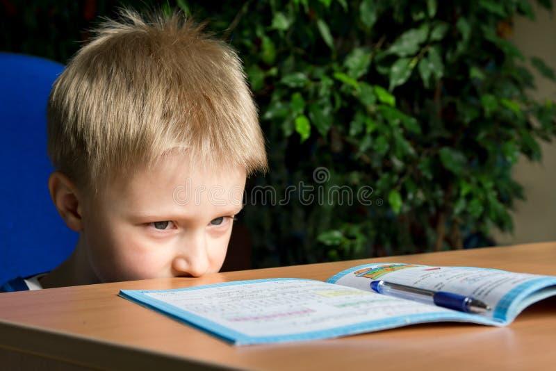 Difficult school homework. Tired boring boy don't want to do his difficult school homework stock photos