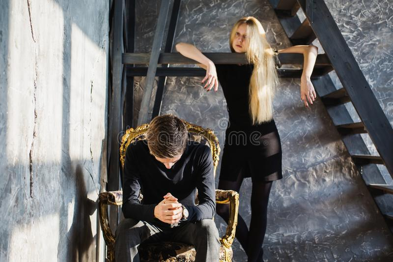 Difficult situation in life. Conceptual photography. A young men and young blonde women with long hair. Problems and difficulties in relations. Difficult royalty free stock photography