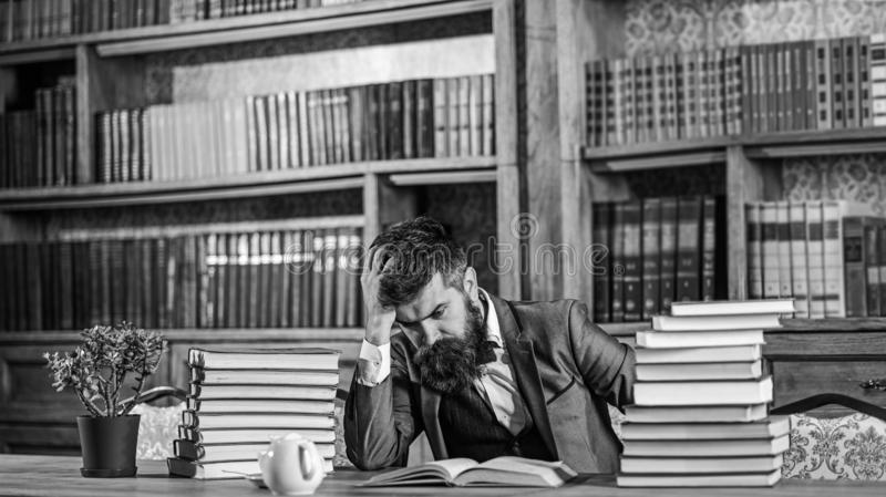 Difficult subject, confusing question, study, education, hard work, intellectual research concept. Man sits at table. With many books. Mature man has serious royalty free stock images