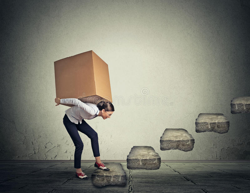 Difficult task concept. Woman carrying heavy box upstairs stock photo