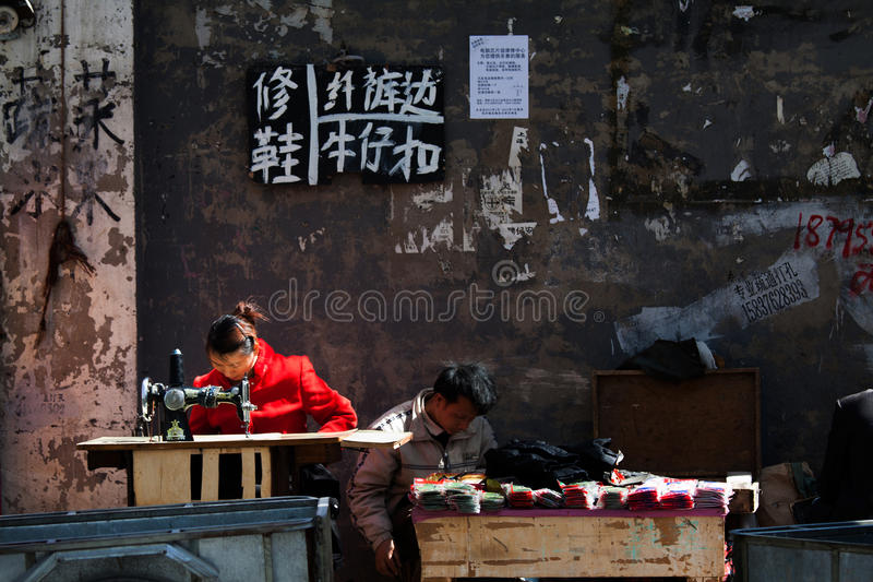 Difficult working place, open tailoring. Poor couple tailors working on tailoring at street corner, making living stock photography