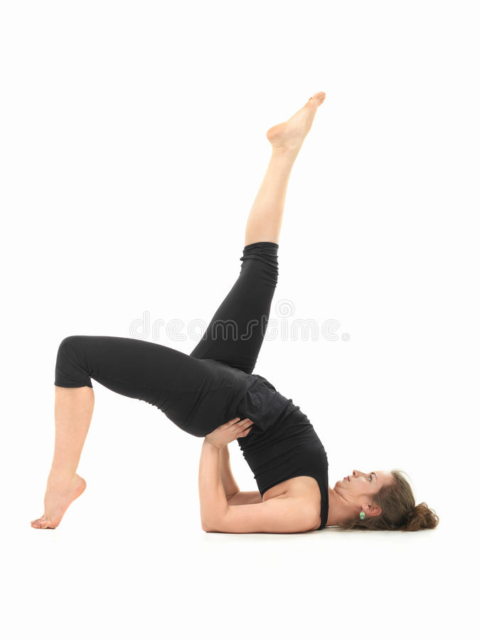 Difficult yoga posture demonstration. Young Caucasian woman in balancing yoga pose stock photos