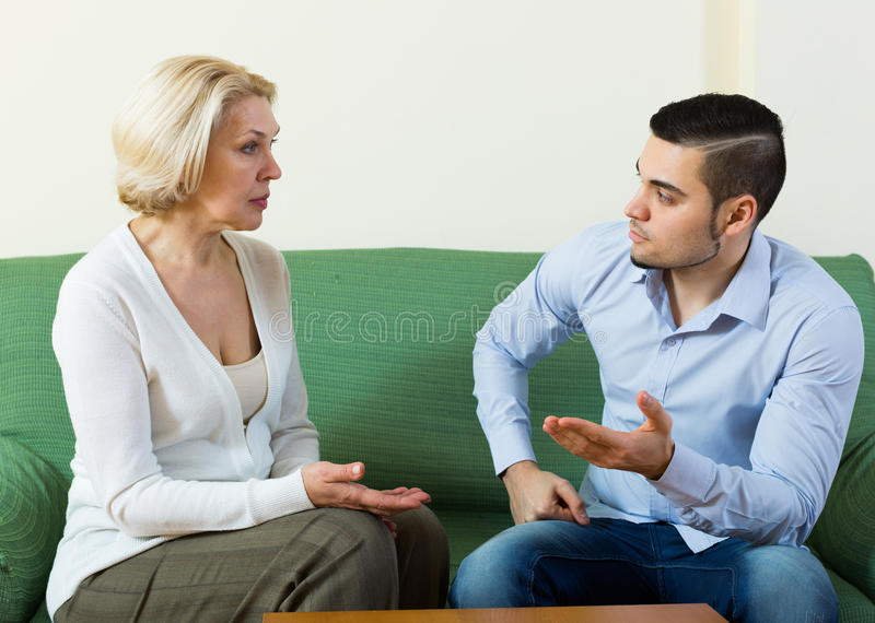Difficulties of communication between son and mother. Difficulties of communication between adult son and mother stock images