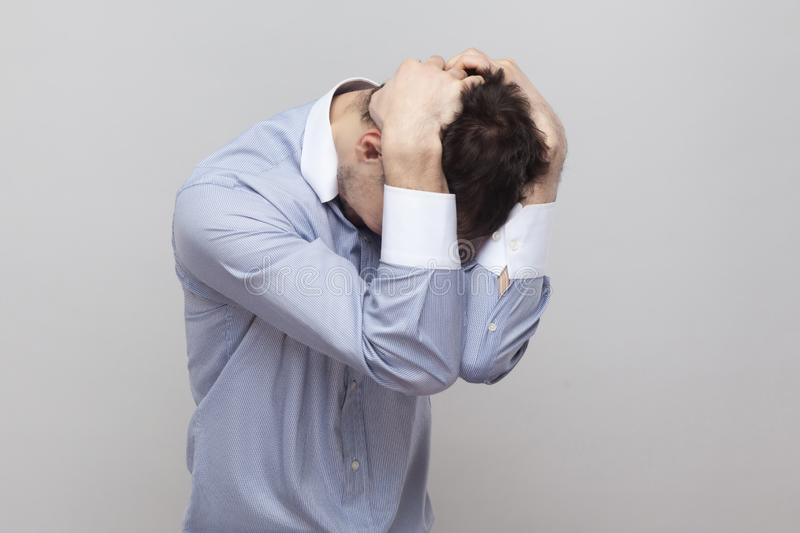 Difficulties, failure or mistake. Portrait of handsome bristle businessman in classic light blue shirt standing and holding his. Head. indoor studio shot stock images