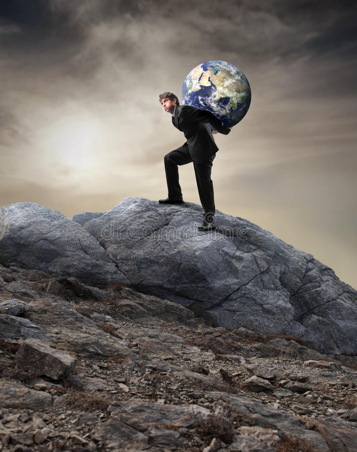 Difficulty. Businessman carrying the earth on his shoulders while climbing a mountain royalty free stock photos