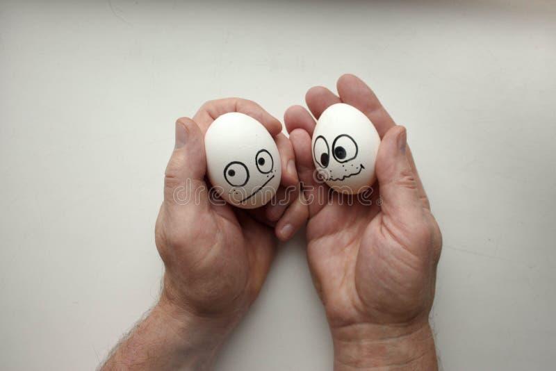 Diffidence pojęcie śmieszni jajka na ręce wpólnie obrazy stock