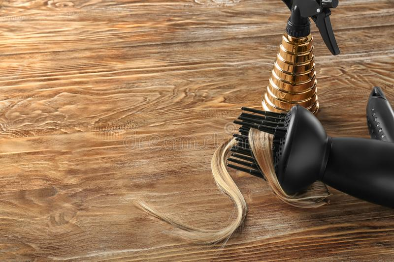 Diffuser hair dryer with strand of blonde hair and spray on wooden background royalty free stock photo