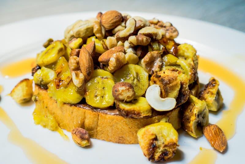 Diffusion croquante de noisette de chocolat sur le pain grillé et écrimage avec la banane, la noix, l'amande, la noix de cajou et photographie stock libre de droits