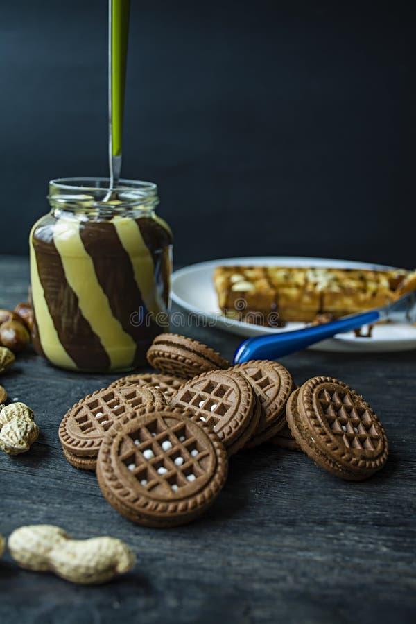 Diffusion de chocolat ou crème de nougat avec des noisettes dans un pot en verre sur un fond en bois foncé photos stock