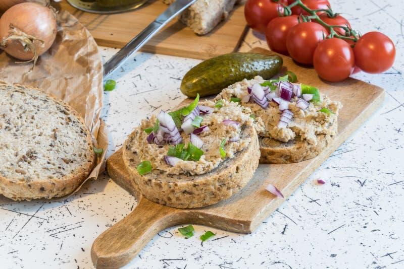Diffusion de porc, saindoux et concombres aigres sur le pain rond frais, arrosé avec le ressort et l'oignon rouge photographie stock libre de droits