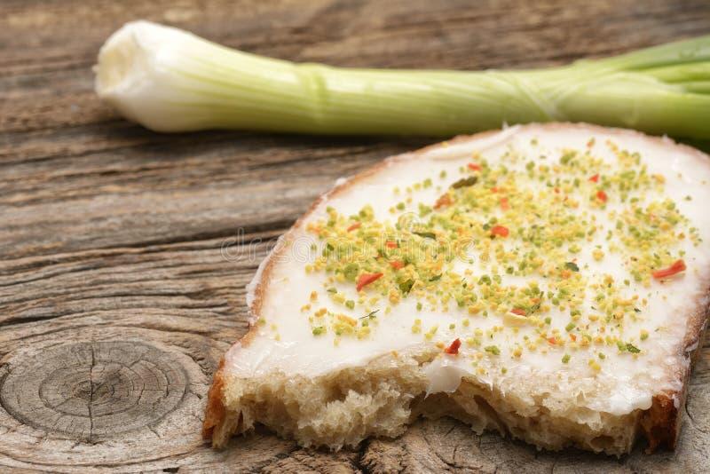 Diffusion de saindoux sur le pain cuit au four à la maison image stock
