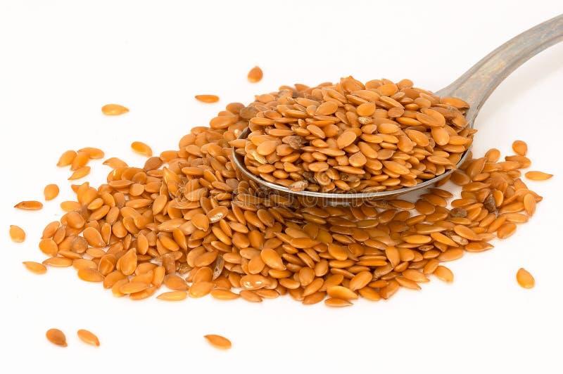 Diffusione del seme di lino ed alcune in cucchiaio fotografie stock libere da diritti