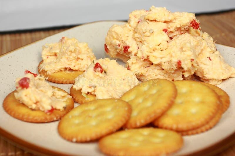 Diffusione di formaggio del pimento sui cracker immagine stock libera da diritti