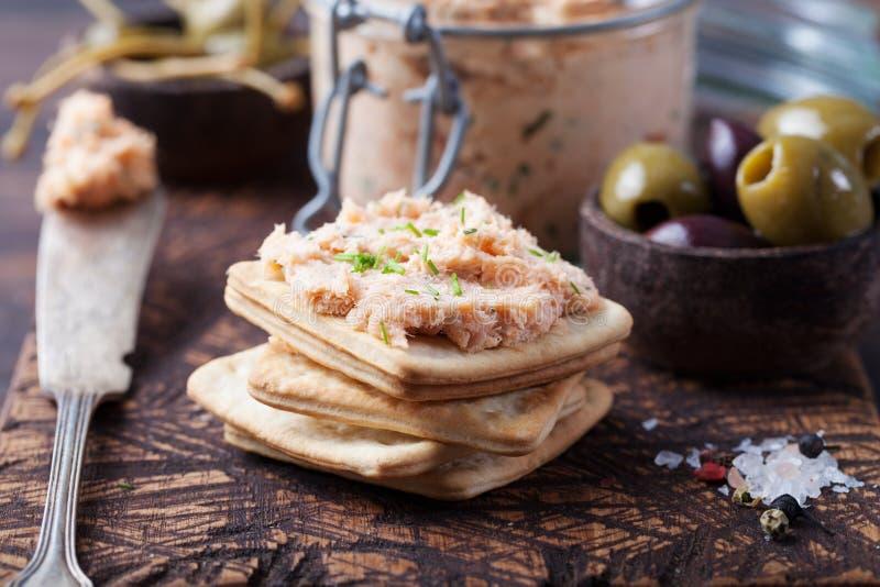Diffusione di formaggio a pasta molle e del salmone affumicato, mousse, patè in un barattolo con i cracker e capperi su un fondo  fotografia stock